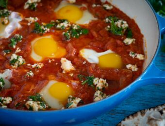 Shakshuka with poached eggs in a blue skillet